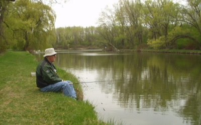 man sitting on bank who is fishing