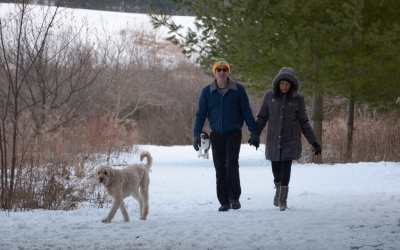 Two hikers with a dog at Prairie Moraine County Park
